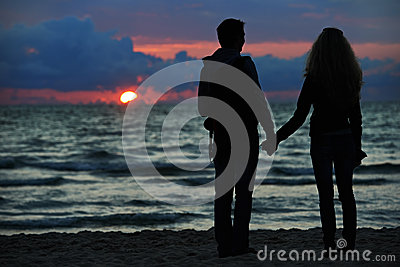 Young family couple at sunset beach