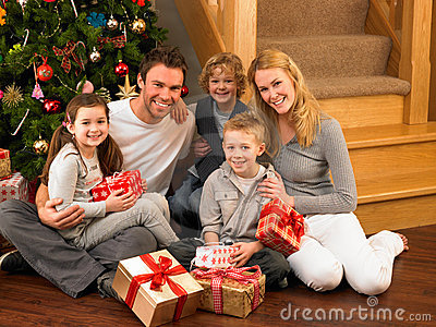 Young family at home exchanging gifts