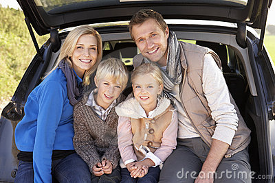 Young family pose together at rear of car