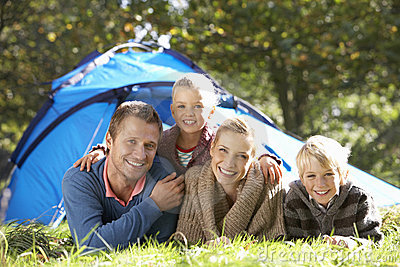 Young family poses outside of tent