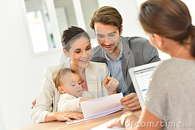Young family in real-estate agency buying new house Stock Photo