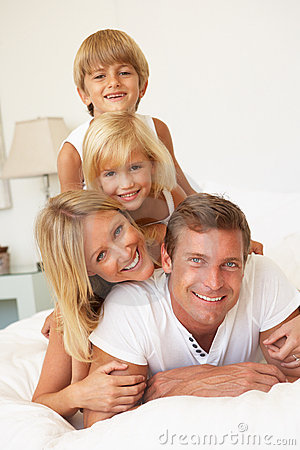 Young Family Relaxing In Bed Together