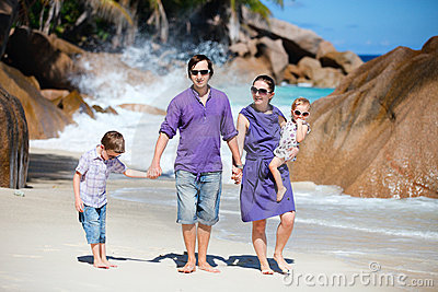 Young family walking along beach