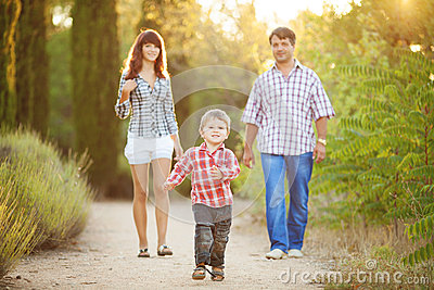 Young family walking in the summer park