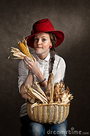 Young farmer girl with a corncob