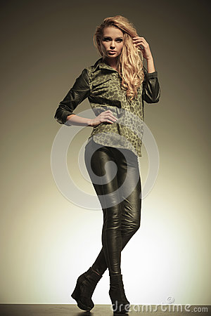 Young fashion blonde woman in leather pants posing