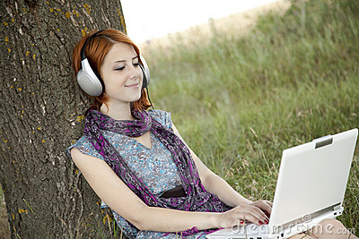 Young fashion girl with notebook and headphones