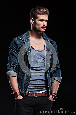 Young fashion man in casual jeans clothes looking away