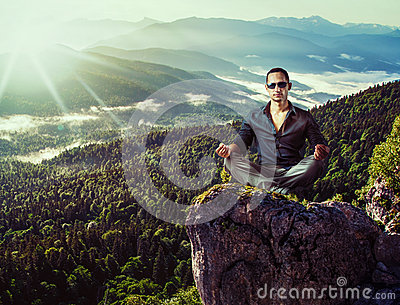 Young fashion man sitting on mountains stone