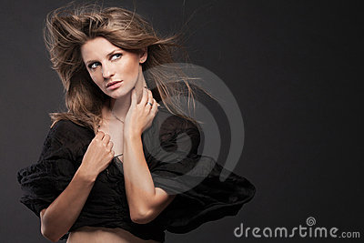 Young fashion model posing on dark background.