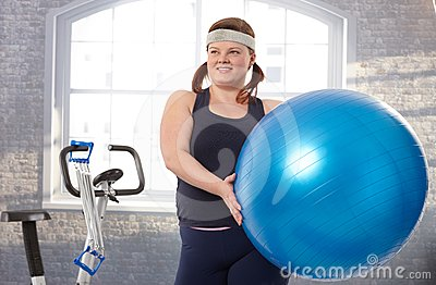 Young fat woman exercising with fit ball