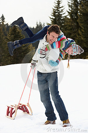Young Father And Daughter In Snow With Sled