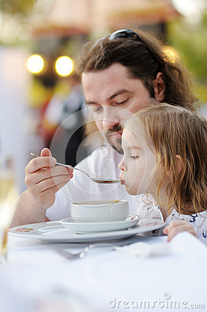Father feeding his little girl