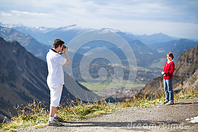 Young father taking picture of his son in mountains