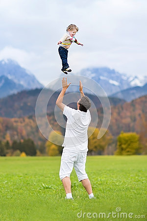 Young father throwing his baby high in the sky