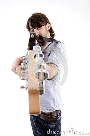 Young fellow holding guitar like gun