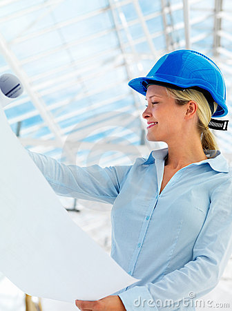 Young female architect holding blue prints
