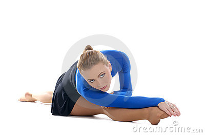 A young female athlete is stretching her legs