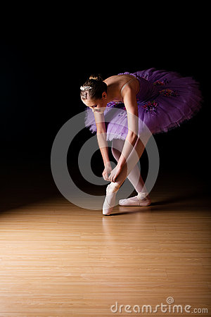 Free Young Female Ballerina Adjusting Her Shoes Royalty Free Stock Photos - 46978538