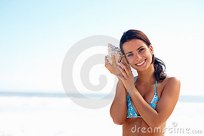 Young female at the beach holding a conch shell