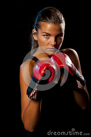 Young Female boxer on black background