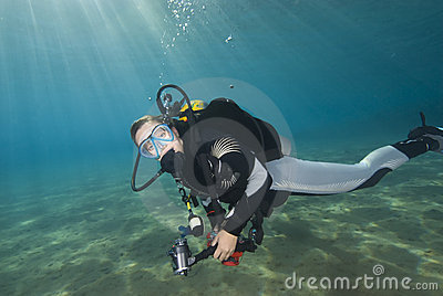 Young female diver in clear blue water.