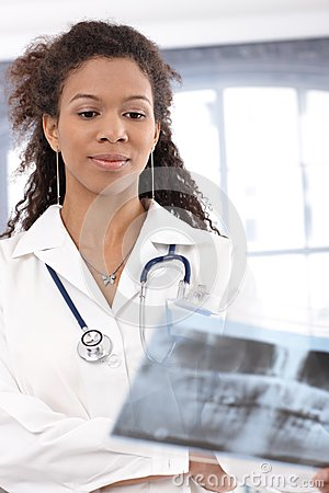 Young female doctor examining x-ray image