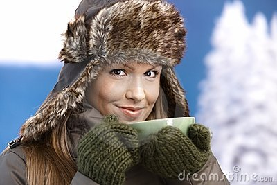 Young female dressed up warm drinking tea smiling