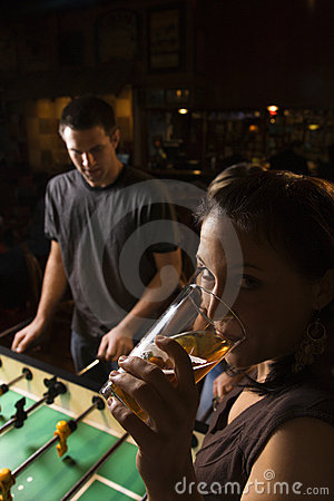 Young female drinking beer at foosball table.