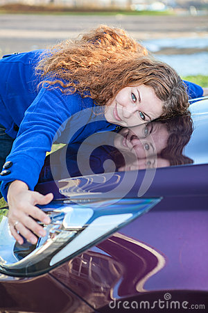 Young female driver hugging hood of vehicle