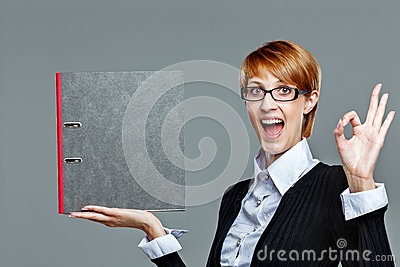 Young female employee gesturing perfect job and holding folder