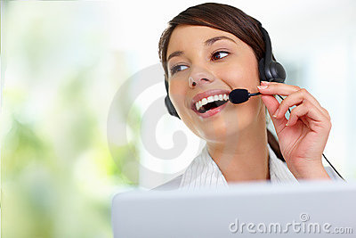 Young female employee talking on  headset