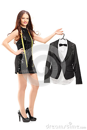 Young female fashion designer holding a bow tie suit on a hanger