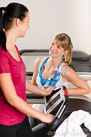 Young female friends chatting in fitness center