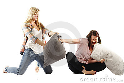 Young female friends enjoying pillow fights