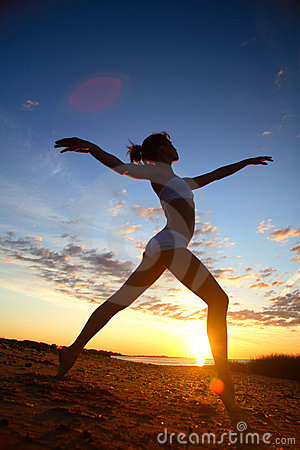 Young female gymnast exercising at sunrise