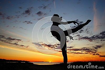 Young female gymnast exercising at sunrise