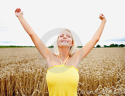 Young female with hands raised in a crop field