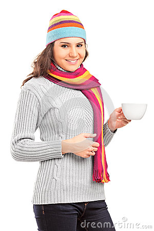 Young female with hat and scarf holding a cup of tea