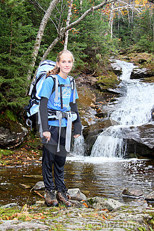 Young female hiker and river cascade