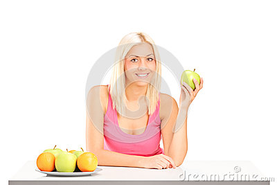 Young female holding an apple during a breakfast