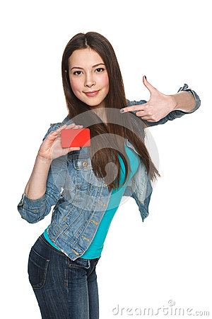 Young female holding blank credit card and pointing at it