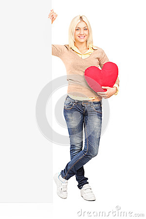 Young female holding a blank panel and red heart