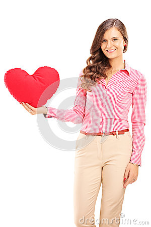 Young female holding a red heart shaped pillow and smiling