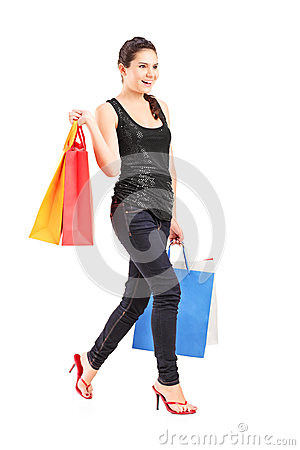 Young female holding shopping bags and walking