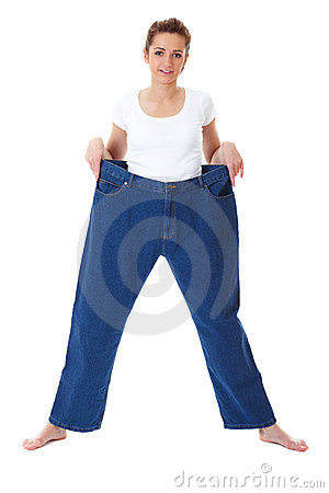 Young female holds her old huge jeans, diet