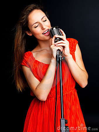 Young female jazz singer singing with retro mic