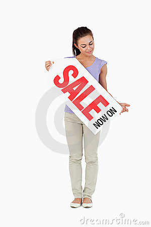 Young female looking at sales sign in her hands
