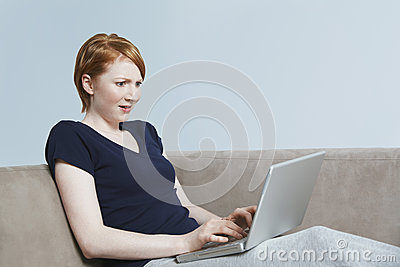 Young Female Looking Surprisingly At Laptop