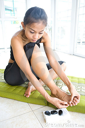 Young female massaging her own foot,